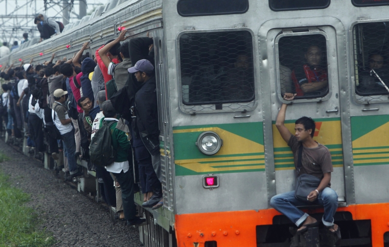People seen outside a commuter train illegally ride the train in Depok, Indonesia's West Java province